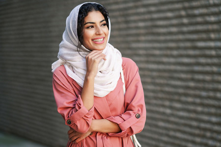 Young Muslim woman wearing hijab headscarf walking in the city center