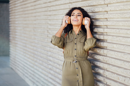 Young Arab Woman walking in the street with wireless headphones