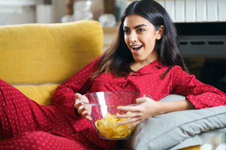 Persian woman at home watching TV eating chips potatoes