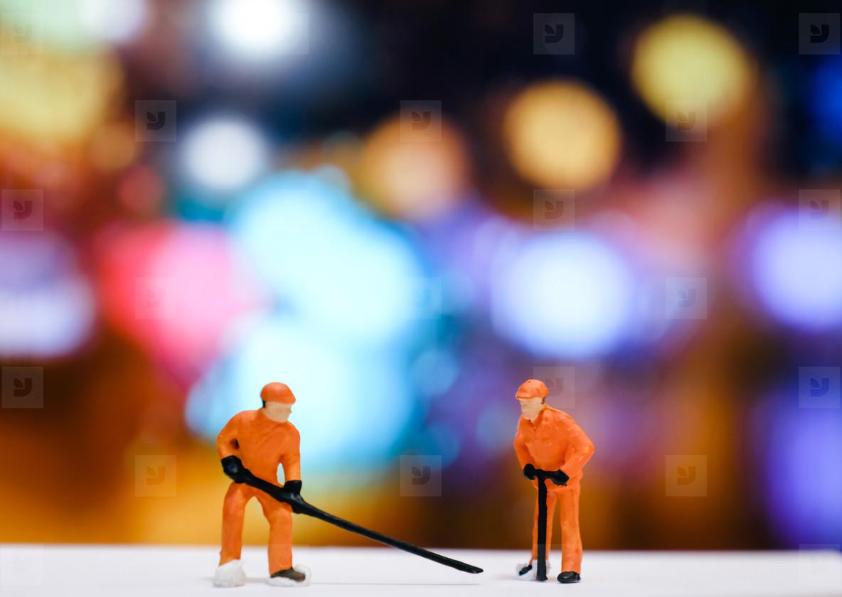 Miniature people worker repair street at night with bokeh light