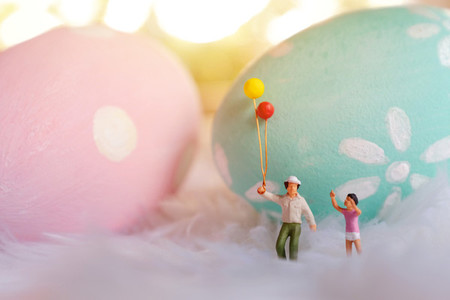 Miniature people family holding balloon with pastel and colorful