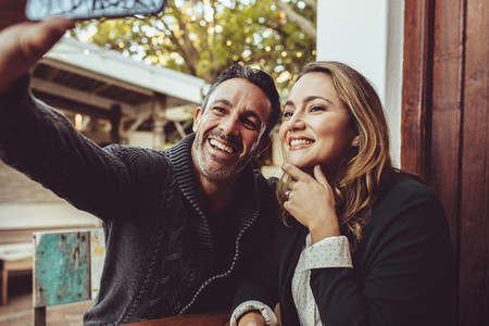 Smiling couple taking selfie at cafe