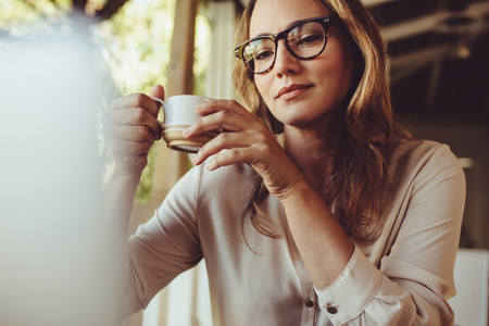 Woman having a coffee while working from a cafe