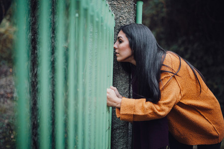 Woman looking through the metal fence in the forest