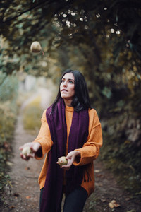 Woman juggling some pears in the field