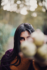 Young woman showing pears at the camera in the forest