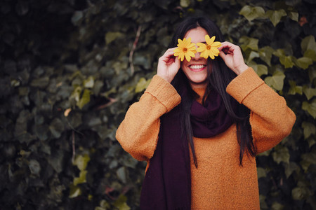 Smiling woman playing with a yellow flower in field