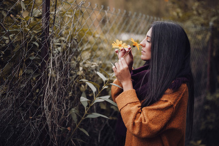 Young woman smelling a yellow flower in the field