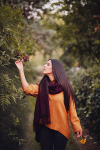 Young woman walking through the forest wearing a orange sweater