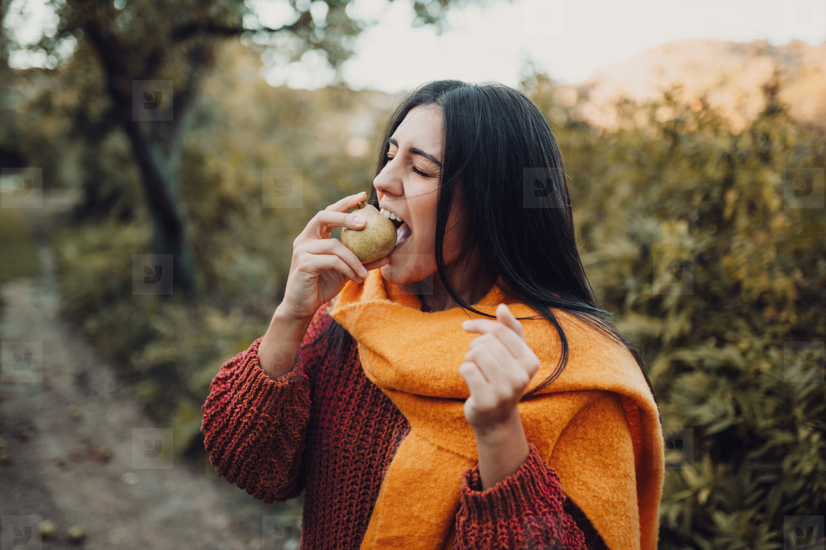 Young woman biting a pear in the field wearing a sweater