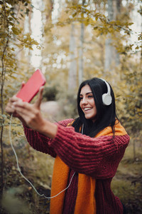 Woman taking a selfie with her phone with headphones