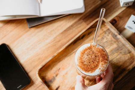 Cup of latte served with glass tube on a wooden  work desk  Coffee break concept