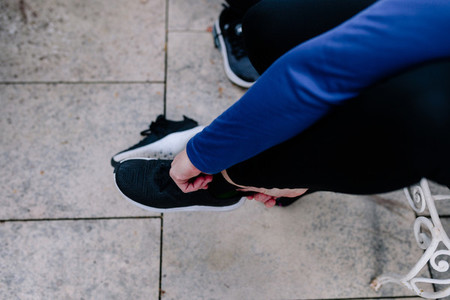 Young sportswoman tying her shoelaces before the training