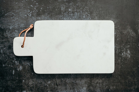 Top down view on an empty white marble cutting board