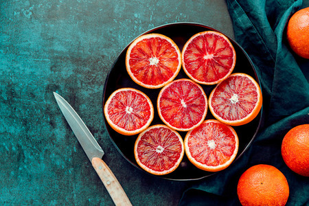 Cutted blood oranges in a plate on a dark blue background Top view copy space