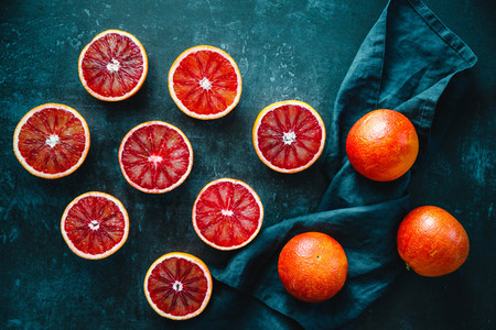 Flat lay food composition with cutted blood oranges on a dark blue background  Top view
