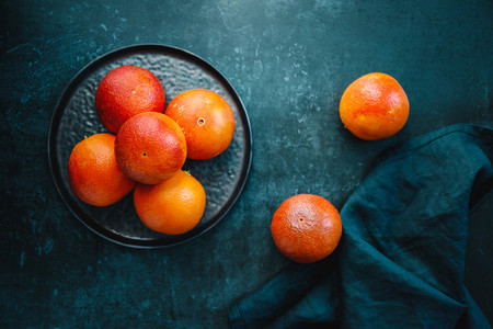 Blood oranges in a plate on a dark blue background  Top view