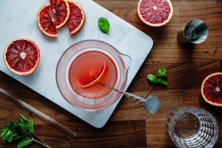 Mixing of refreshing cold summer cocktail with blood orange in a glass pitcher on a marble tray Top view flat lay composition