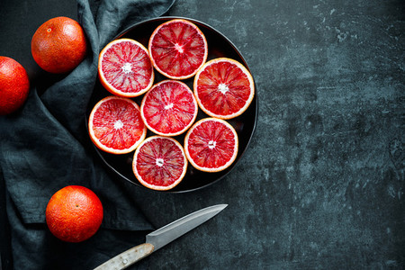 Cutted blood oranges in a plate on a dark black background  Top view  flat lay composition  copy space