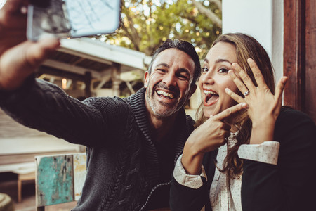 Beautiful engaged couple making selfie