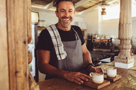 Male barista serving coffee to customers