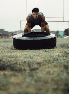Muscular athlete doing a tire flip workout