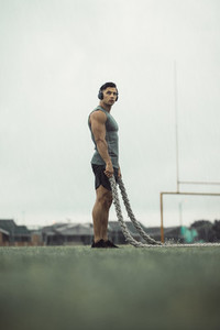 Man taking rest from battle rope workout