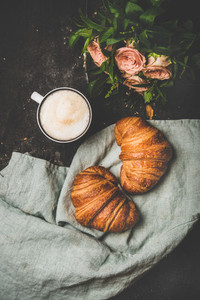 Coffee break with cappuccino croissants and spring flowers