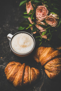 Cup of cappuccino  fresh croissants and bouquet of pink flowers