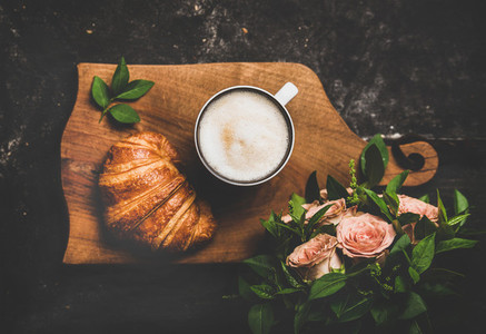 Cup of cappuccino croissant and pink flowers over black background