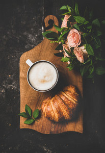 Cup of cappuccino  croissant and bouquet of pink flowers