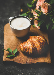Coffee break with cappuccino  croissants and pink spring flowers