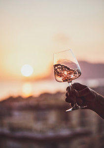 Mans hand holding rose wine with sea at background