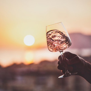 Glass of rose wine in hand with sunset at background