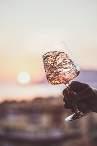 Glass of rose wine and sunset at background