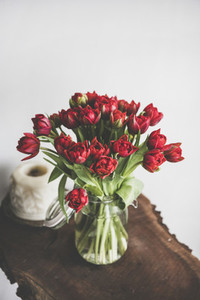 Bouquet of fresh Spring red tulips on rustic wooden table