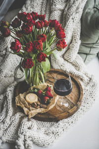 Red wine snacks and red tulips over knitted blanket