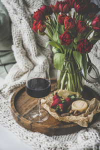 Glass of red wine  snacks and tulips over knitted blanket