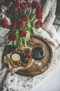 Glass of red wine snacks and tulips on wooden board
