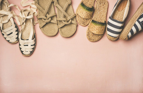 Variety of trendy summer shoes over pastel pink background