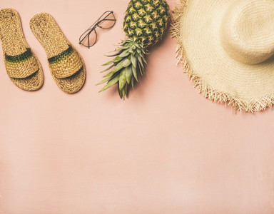 Variety of summer apparel items and fresh pinapple copy space