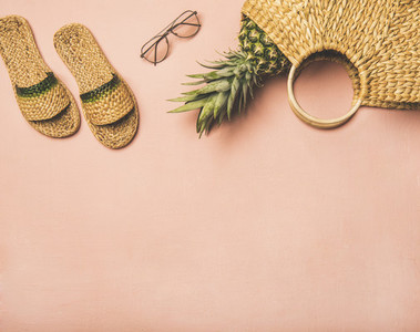 Summer apparel items and fresh pinapple over pink background