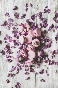 Sweet macaron cookies and rose buds and petals vertical composition