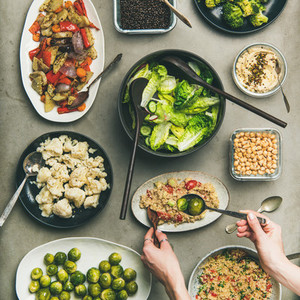 Healthy vegan dishes and woman hands taking couscous squqre crop