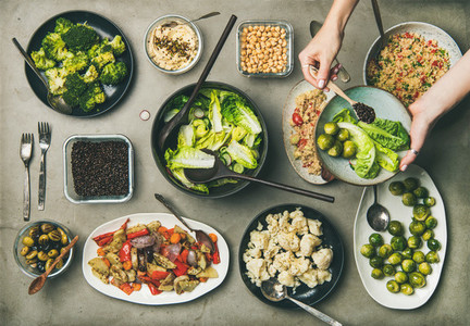 Healthy vegan dishes and woman hand adding ingredients to plate