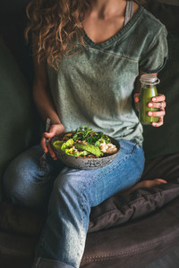 Woman sitting and holding healthy superbowl and smoothie