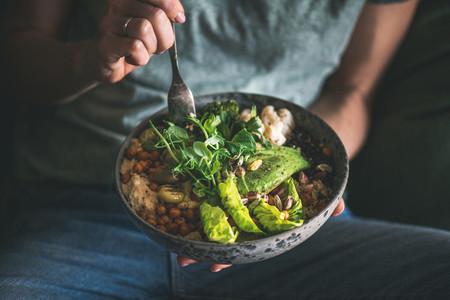 Woman eating healthy vegan dish from bowl