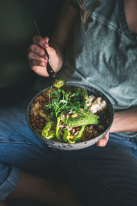 Woman sitting and eating healthy vegan dish from bowl