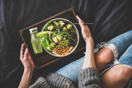 Healthy vegan bowl in bed smoothie and woman in jeans