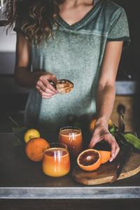 Woman making fresh blood orange juice or smoothie in kitchen